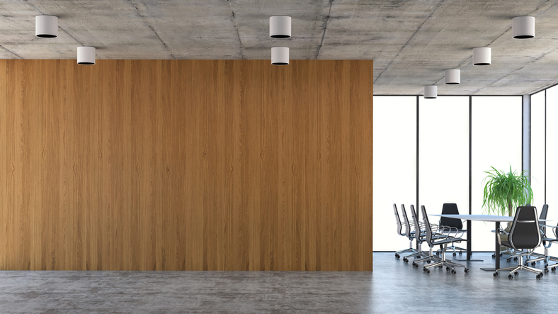 An empty office, featuring a wood wall, table, and chairs