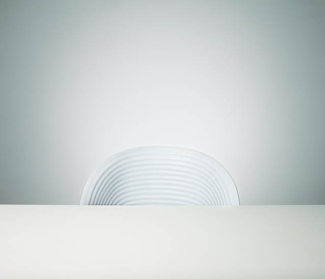 A white chair and white desk sitting against a white wall