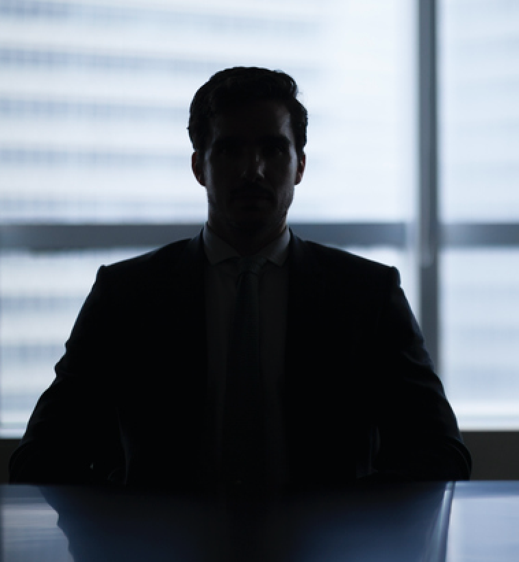 A business man's silhouette in a dark room