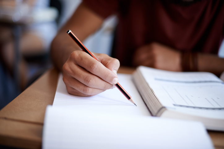 Student writing an exam with a pen and paper